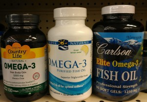 Three bottles of omega-3 supplements by different manufacturers -- Carlson, Country Life, ad Nordic Naturals.