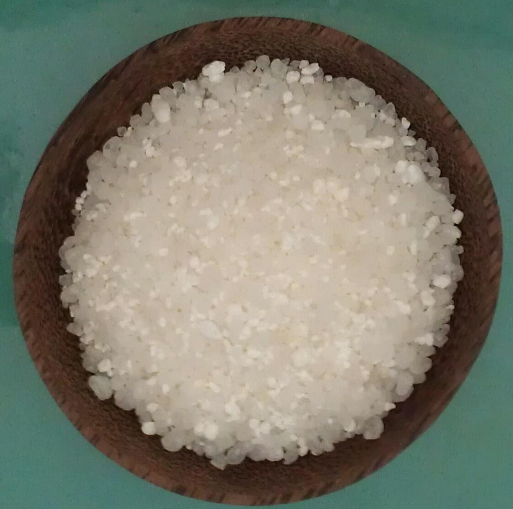Dead Sea Salt in Coconut Bowl on Sea Blue Background. Dead sea salt is full of minerals that can revitalize and replenish you.